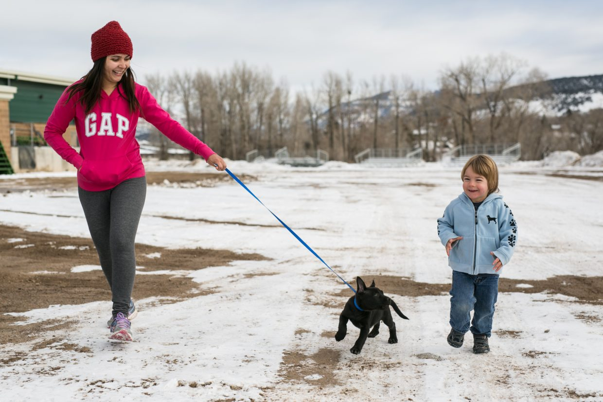 Ana Paula, of Brazil, left, and Connor Jones keep one of the puppies stranded at the Eagle River Center company on Friday.