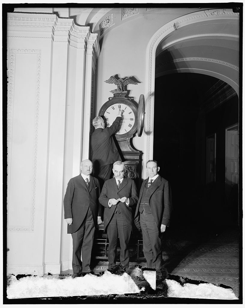 Senate Sergeant at Arms Charles Higgins turns forward the Ohio Clock for the first Daylight Saving Time in 1918 in the U.S. Capitol while Sens. William Calder New York