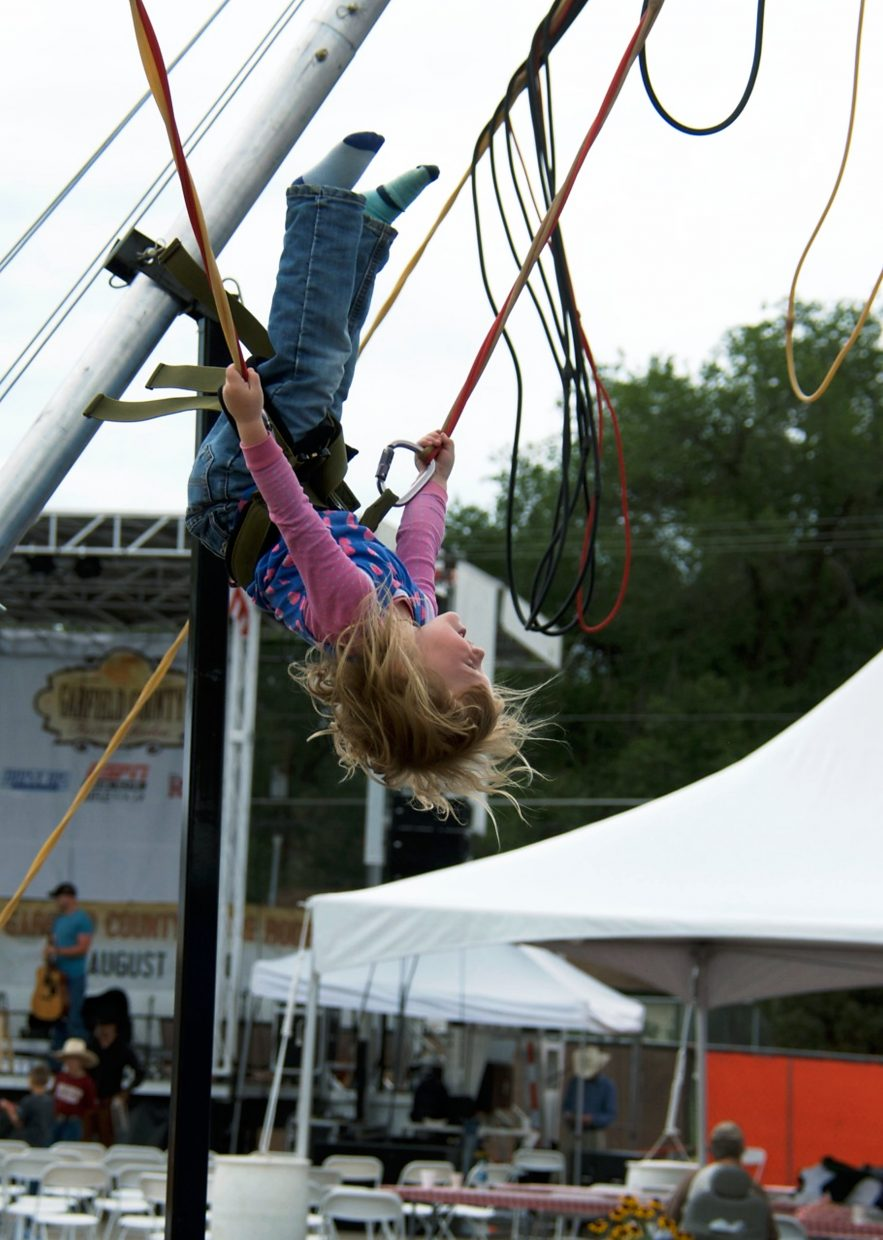 Cada Jenkins, 3, executes a perfect backflip on the Spider Jump at the Garfield County Fair on Friday afternoon.