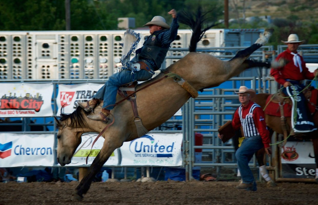 Shea A. Hardwick, from Laramie, Wyo., held onto Daisy in the bareback bronc riding competition during the PRCA Rodeo at the Garfield County Fairgrounds.