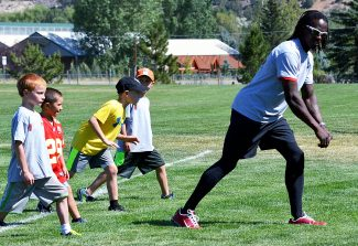 San Francisco 49ers wide receiver Brandon Lloyd works with children on proper line-of-scrimmage techniques during the third-annual Brandon Lloyd Football camp at Crown Mountain Park in El Jebel on Thursday.