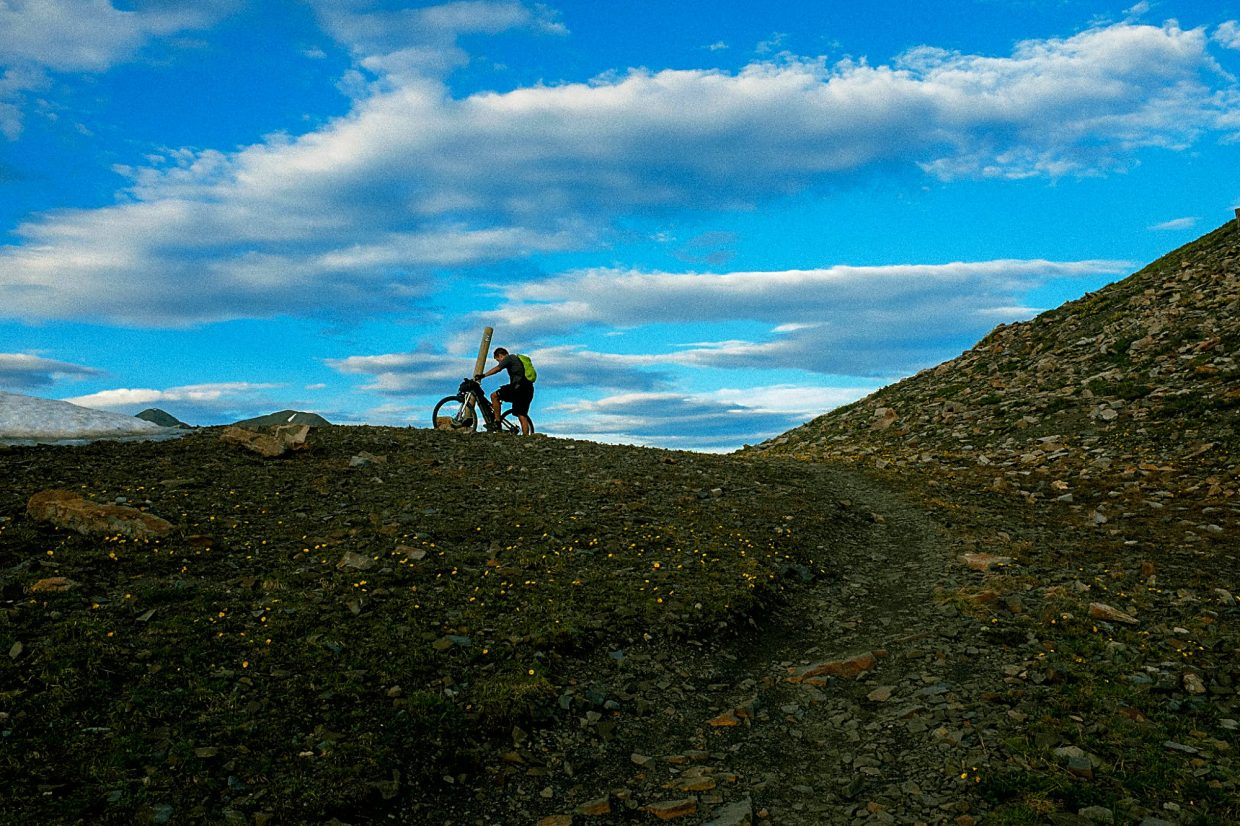 A cyclist in the Colorado Trail Race pushes his bike over one of many passes.