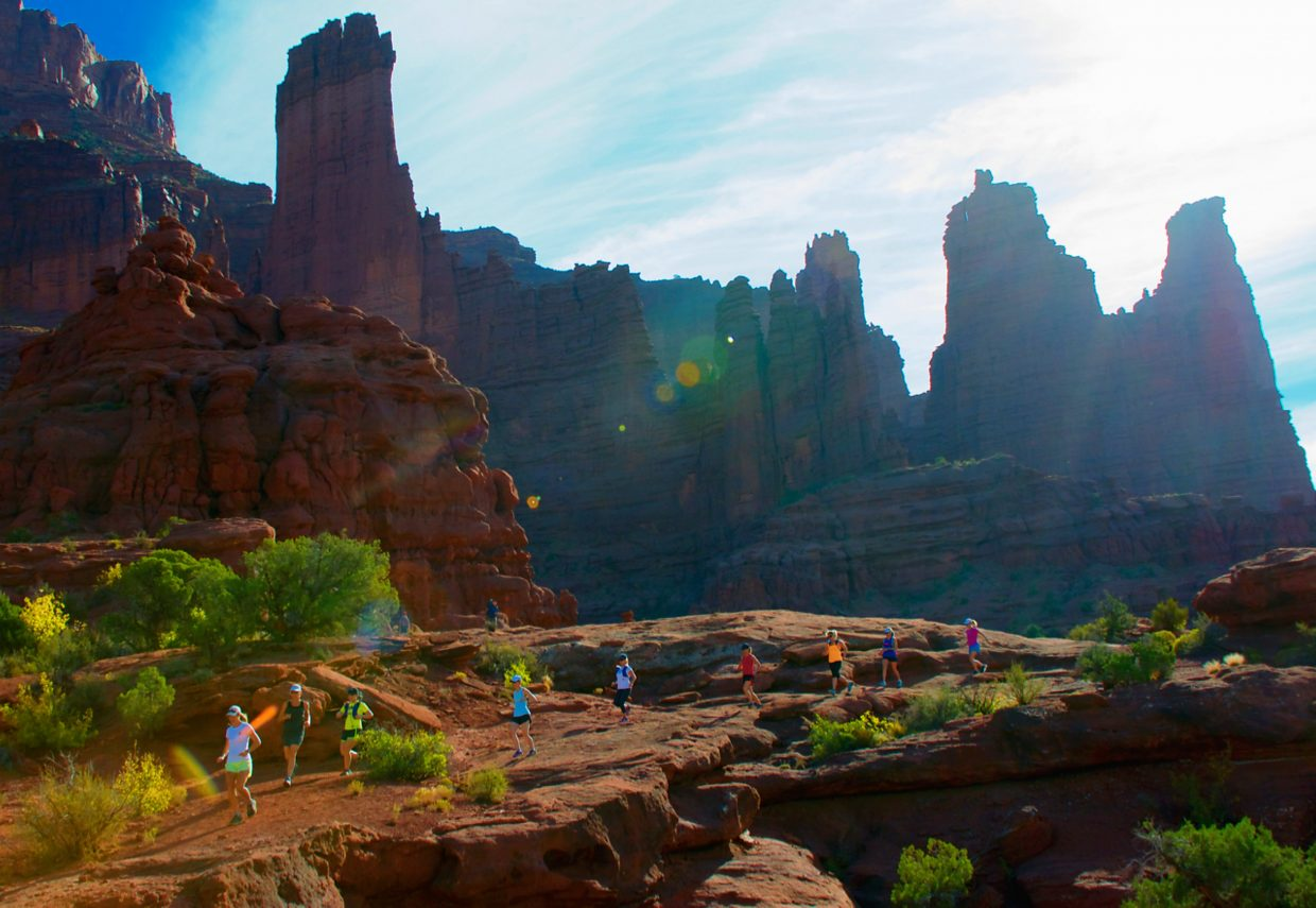 A group of women runs the Fisher Towers trail outside of Moab.