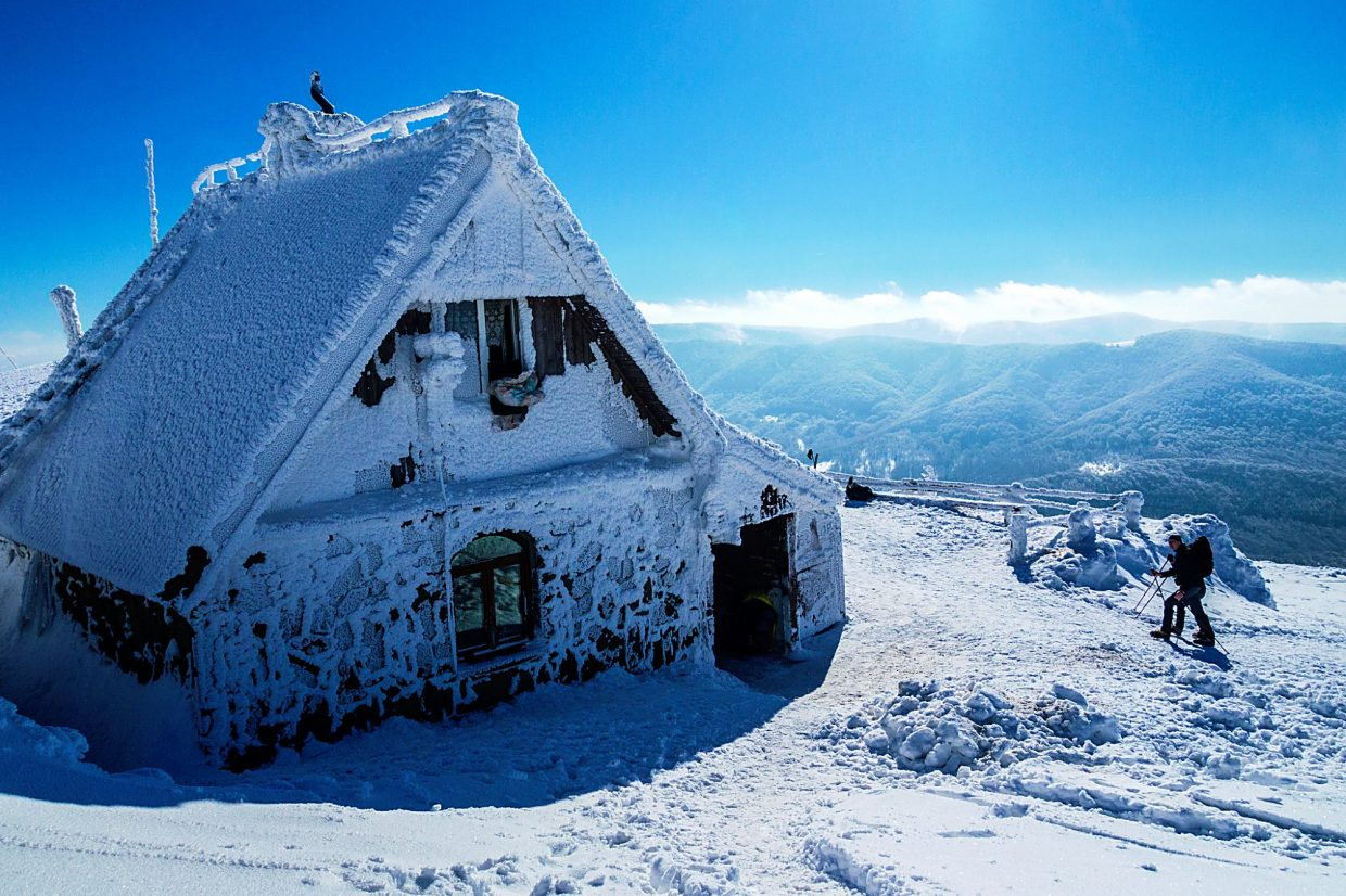 Skiers arrive at a frozen hut.