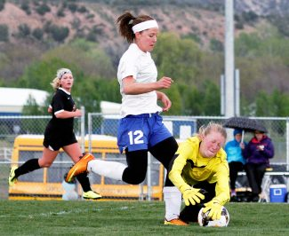 Grand Valley High School goalie Erin Schuckers collides with Paige Ryan of Coal Ridge as Schuckers dives to stop the ball during the first half of Saturday's Class 3A state playoff game at The Pasture. Ryan scored three goals during the Titans' 4-0 victory over the Cardinals.