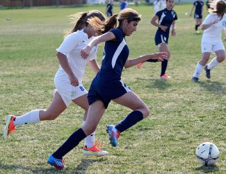 Rifle's Karen Garcia carries the ball up the sideline past Alex Hamilton of Moffat County during Monday's nonleague game in Craig. Moffat County won the game, 6-0.