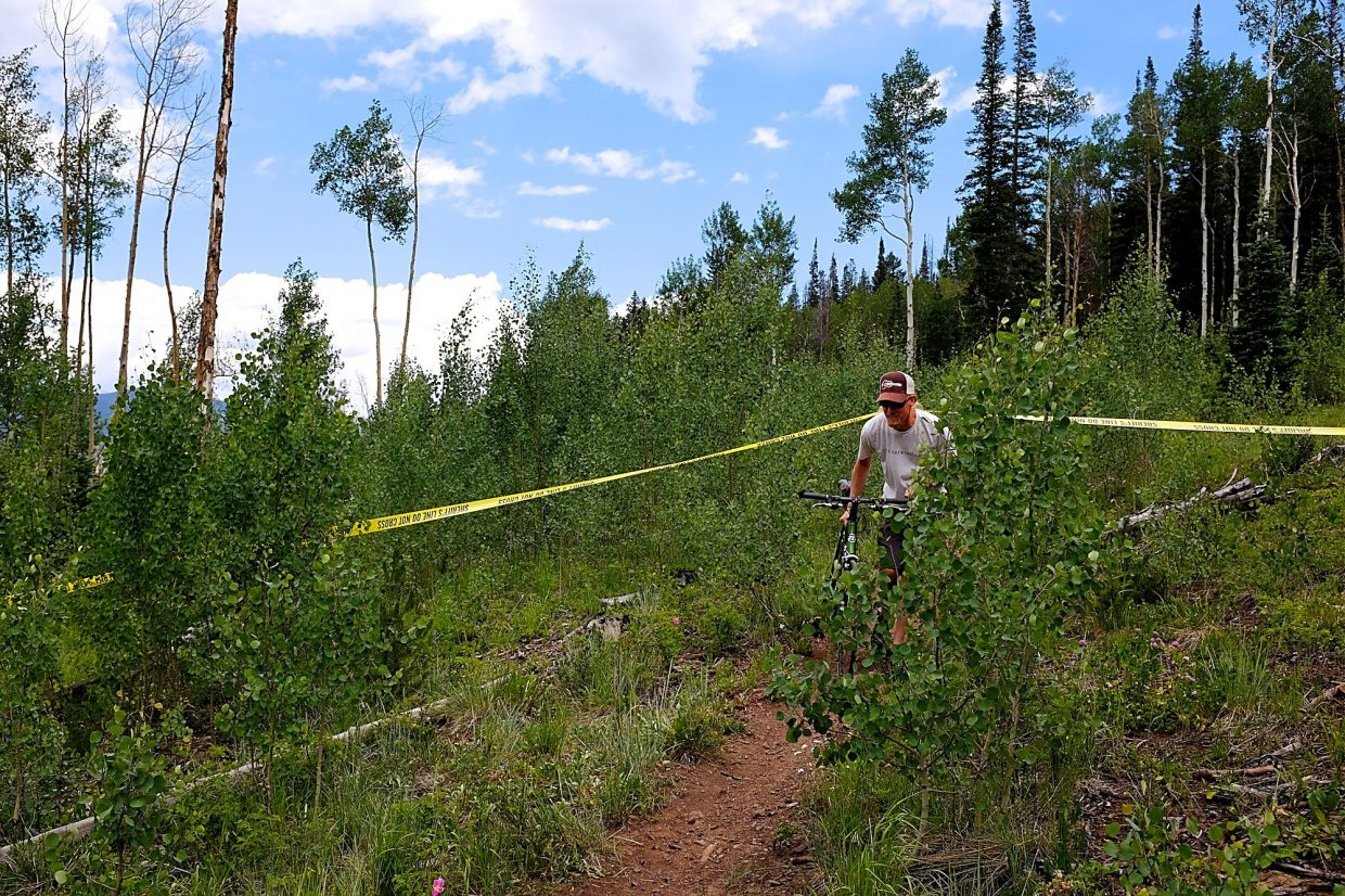A mountain biker ducks under police tape that was set out on the trail just behind St. Anthony Summit Medical Center, which was the scene of a deadly helicopter crash on Friday.