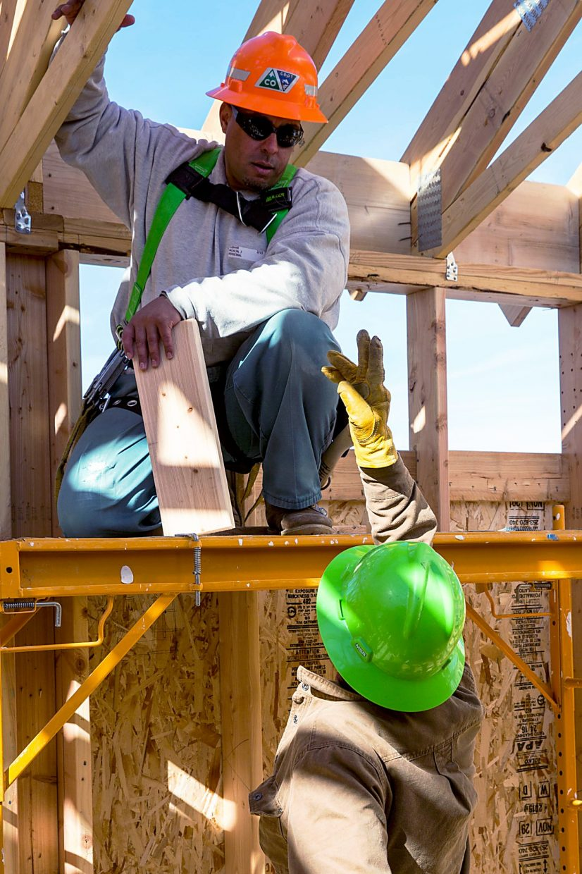 Workers discuss strategy Thursday while building a Habitat For Humanity house in Carbondale.