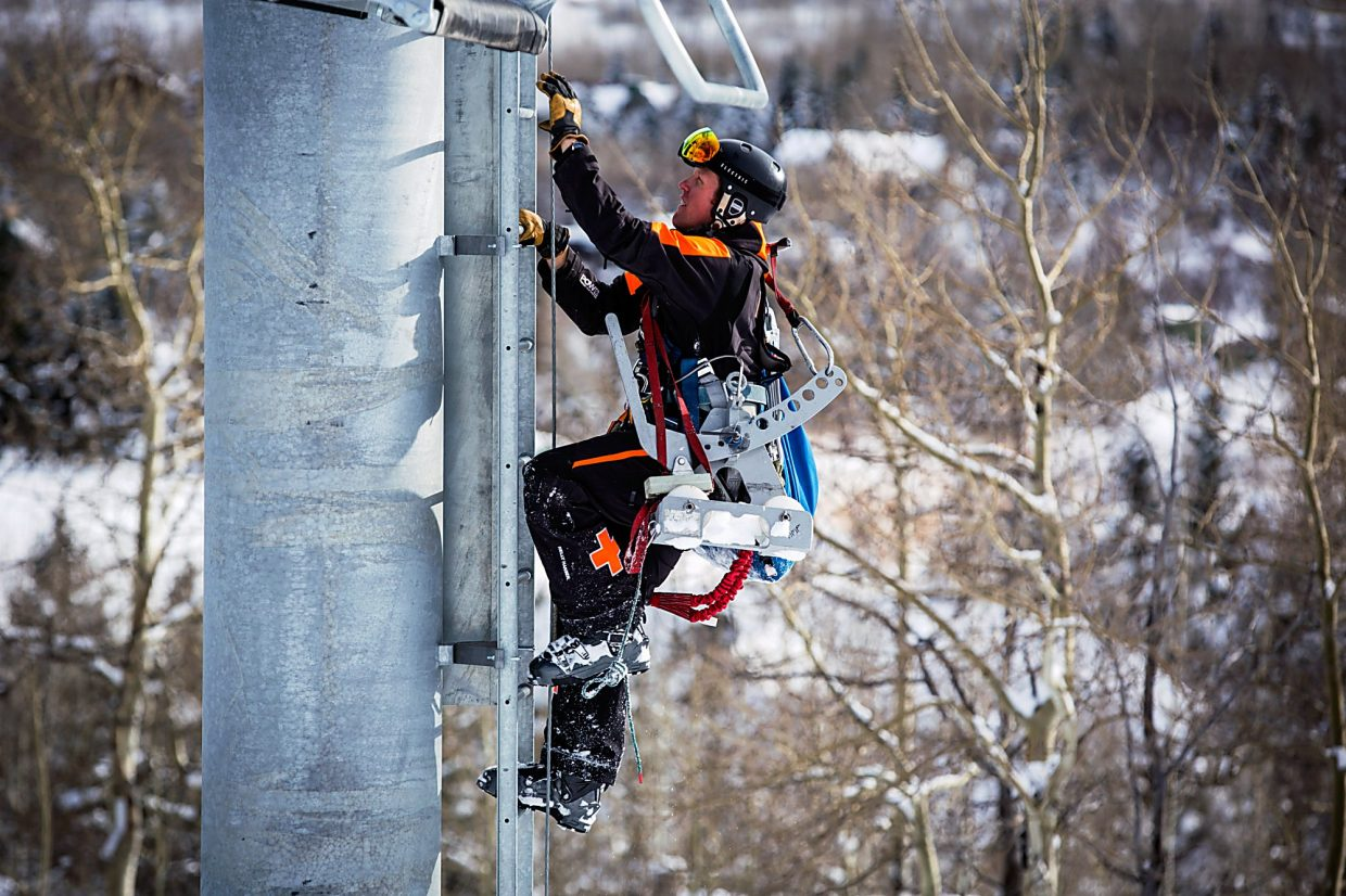 A ski patroller climbs a lift tower on the Tiehack lift at Buttermilk to evacuate a skier due to lift mechanical errors.