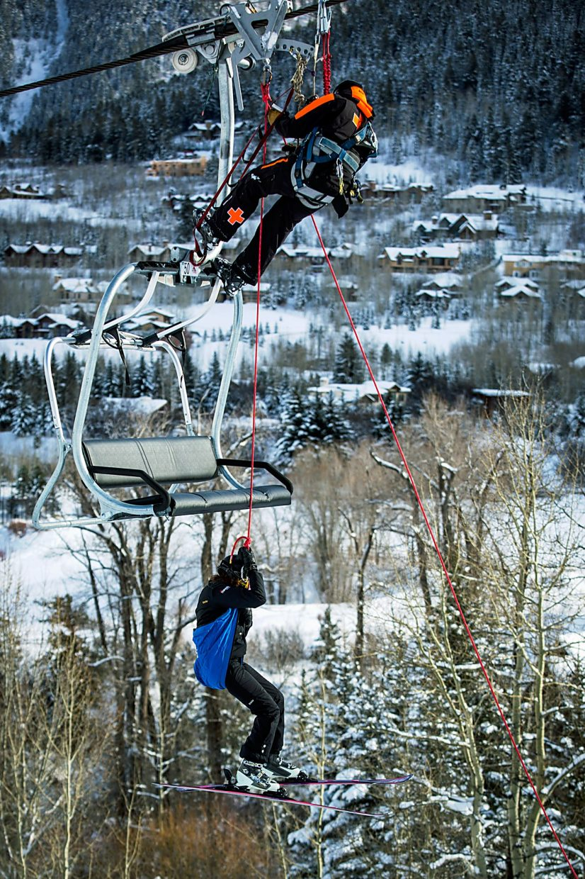 A skier gets belayed off the chairlift onto the ground below.