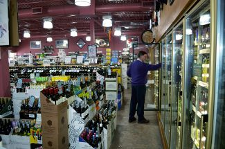 Roaring Fork Liquors owner Ken Robinson shows off the refrigeration and lighting upgrades in his store.