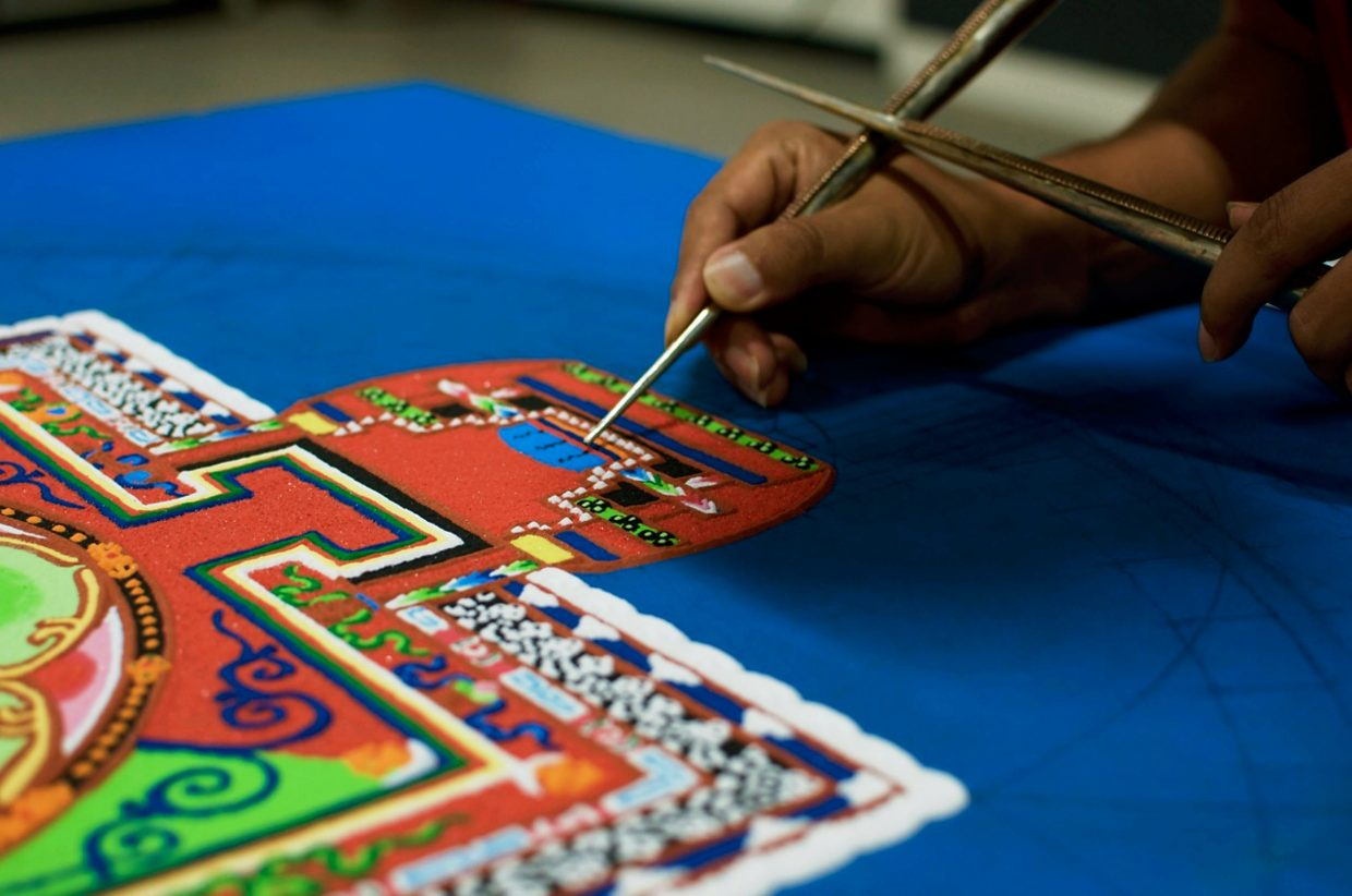 The Venerable Tsundu, a Tibetan monk, works on the sand mandala being created at the Third Street Center. Grains of colored sand drop from a tiny hole in this funnel to create intricate patterns.