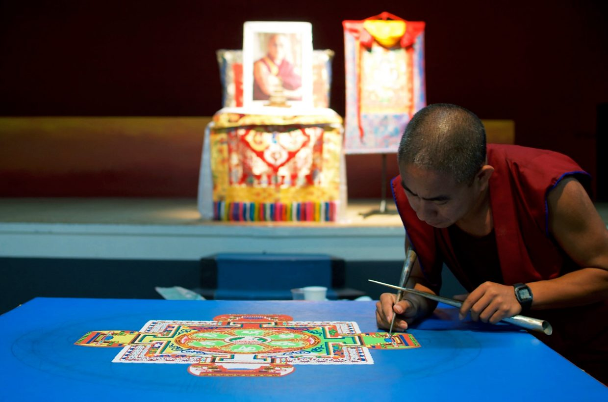 The Venerable Tsundu, a Tibetan monk, works on the sand mandala being created at the Third Street Center.