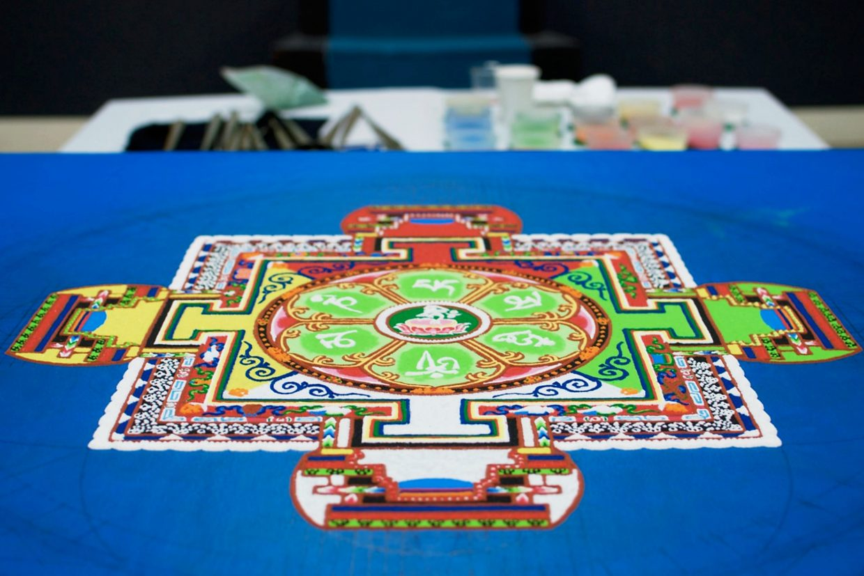 The mandala is made from different-colored sand (in background). It sits on a table in the gym at the Third Street Center.