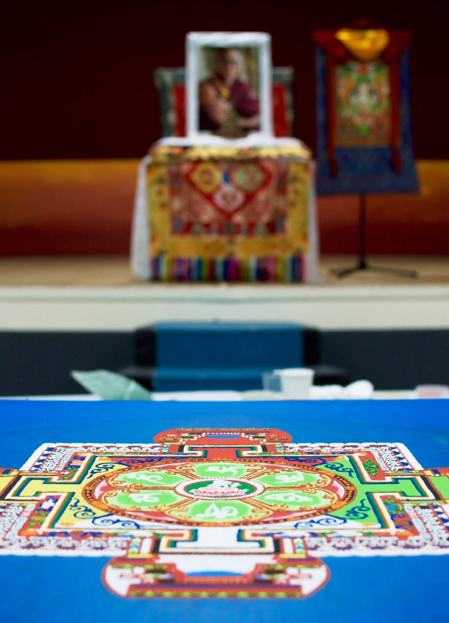 The mandala is placed in front of a picture of the Dalai Lama.