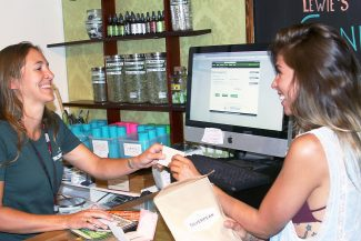 Zoe Higgins, left, a budtender at Silverpeak Apothecary, sells a $40 portion of medical marijuana to customer April Morlock from Aspen on Thursday.