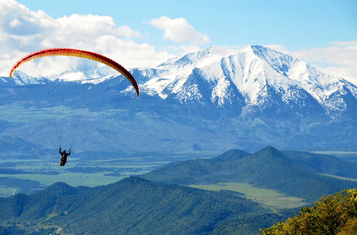 A guide from Glenwood Springs' Adventure Paraglide company soar with a guest riding tandem above the valley on a beautiful summer day.