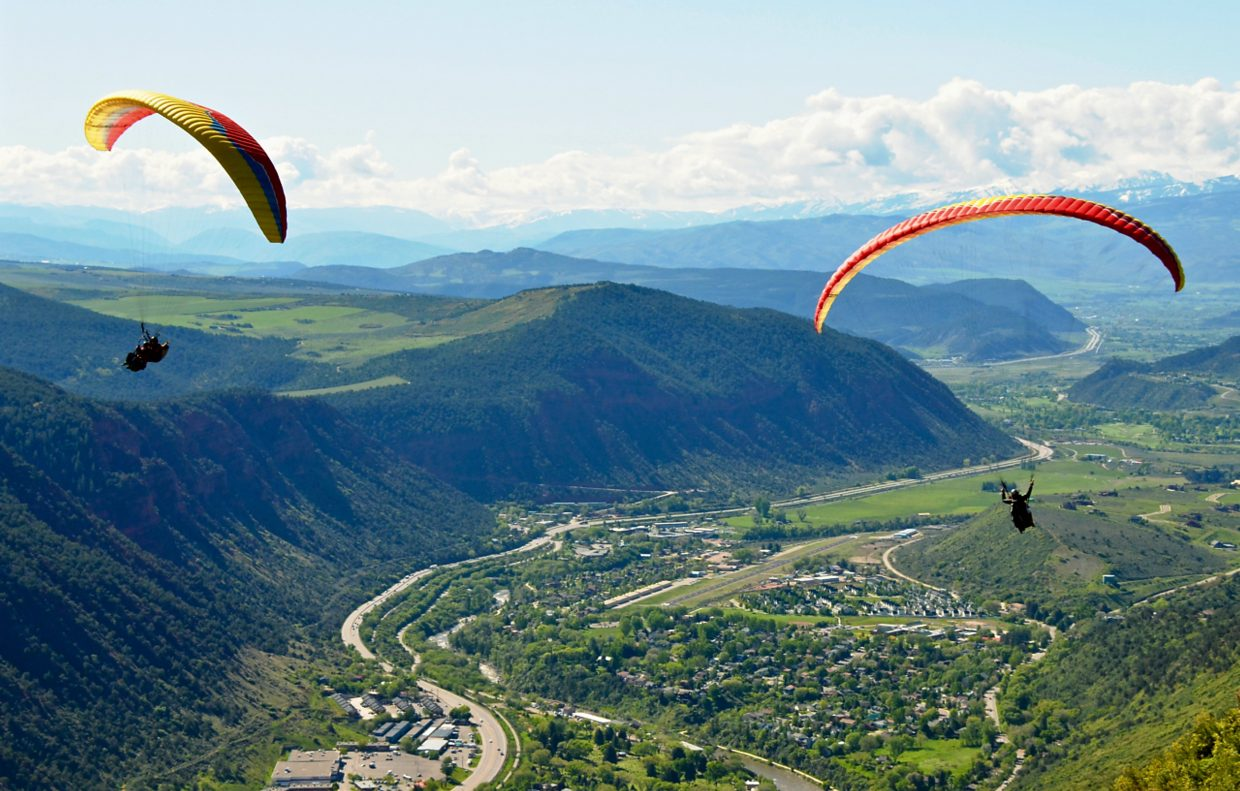 Guides from Glenwood Springs' Adventure Paraglide company soar with their guests above the valley on a beautiful summer day.