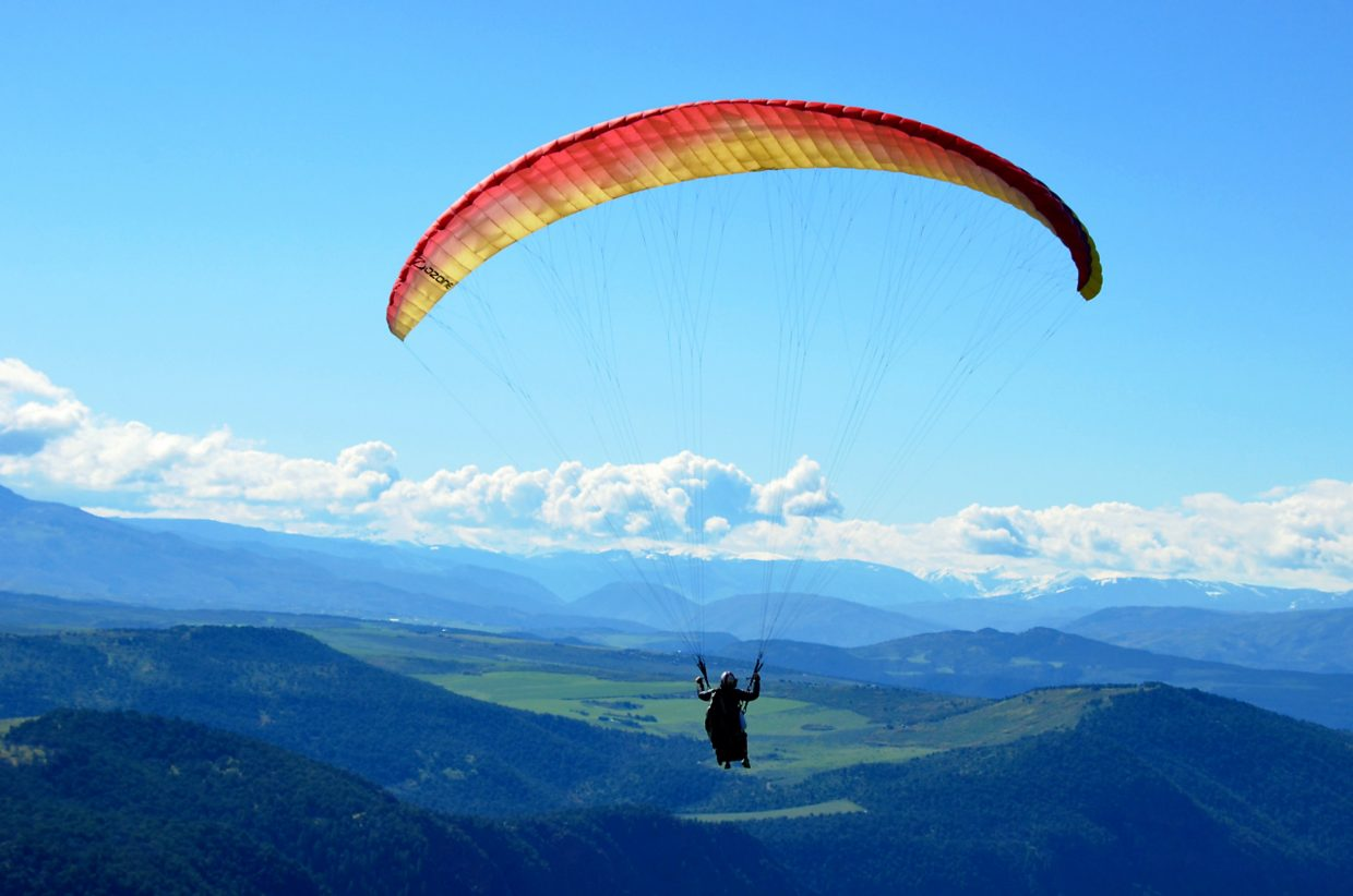 A guide from Glenwood Springs' Adventure Paraglide company soar with a guest above the valley on a beautiful summer day.