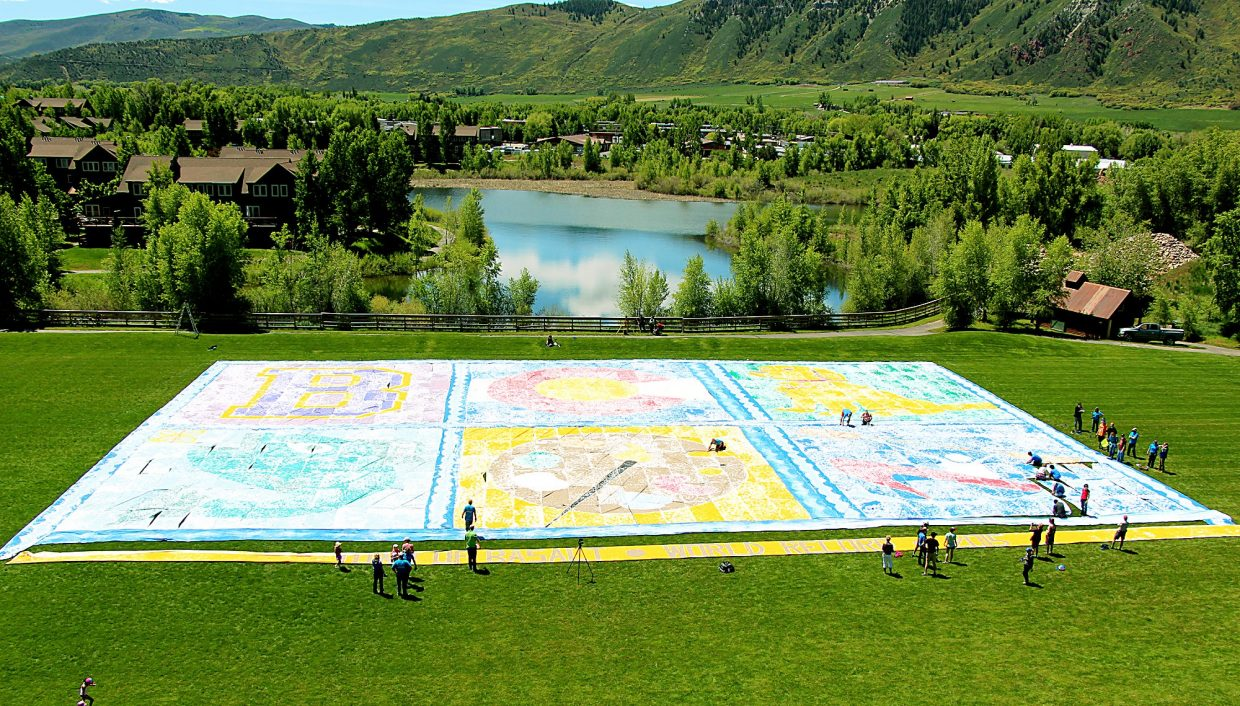 A bird's eye view from a Holy Cross Energy boom truck shows the assembly of Basalt's Guinness World Record footprint painting Saturday at Willits Rugby Field.