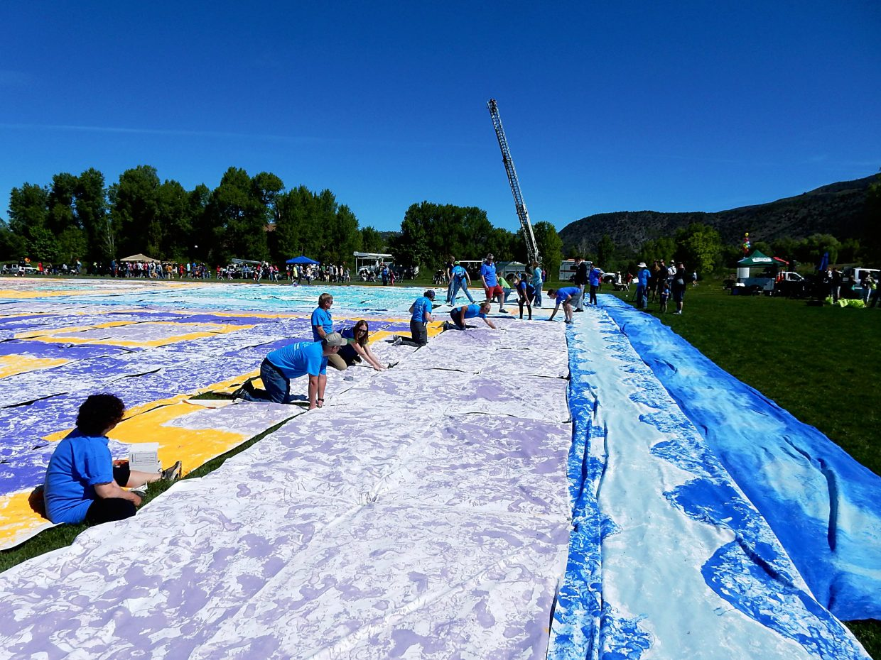 Workers pull 560 muslin panels together Saturday to assemble Basalt's 21,753-square-foot painting made entirely of footprints.
