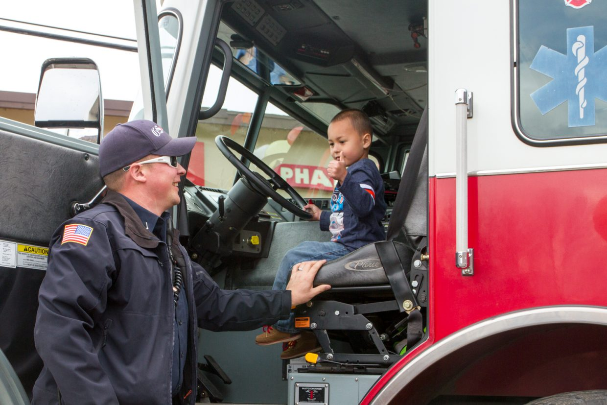 Elijah Montgomery (4) got to sit in the driver's seat of the Glenwood Springs Fire truck with the assistance of Jason Grosse during a fundraiser for the Children's Miracle Network that Rite-Aid is hosting. Donations of $1 were made to have photos taken with the Glenwood Springs fire and police department staff and vehicles. RIte-aid will be taking donations in the store through the end of April and are also holding a competition to guess the number of jelly beans in a jar for a $1 donation; the winner gets to take home the jelly beans.