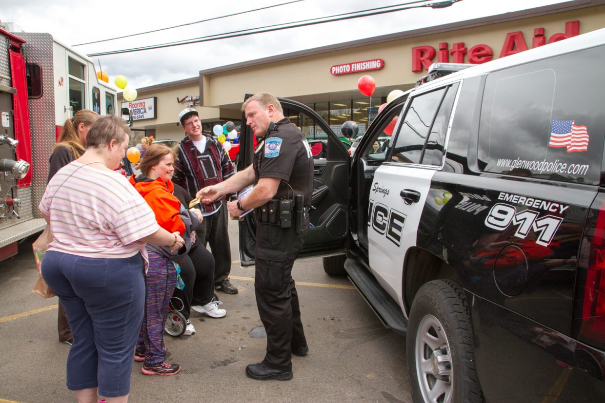 John Hassell of the Glenwood Springs Police Department handed out stickers and invited fundraiser participants to sit in and view the inside of the patrol car during Rite-Aid's fundraiser for the Children's Miracle Network.