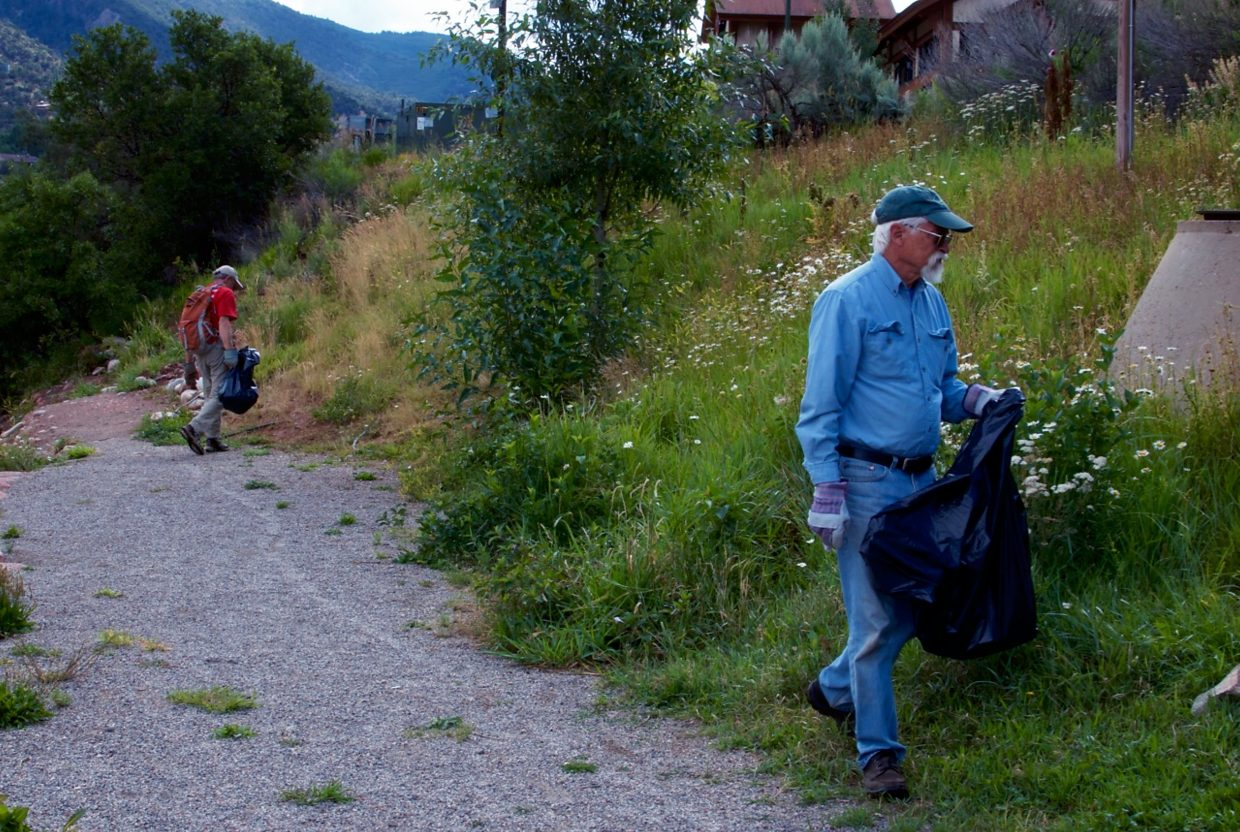 Tom Bohannon (left) and Don Gorman (right) pick up trash along the side of the river near the Glenwood Springs Whitewater Park.
