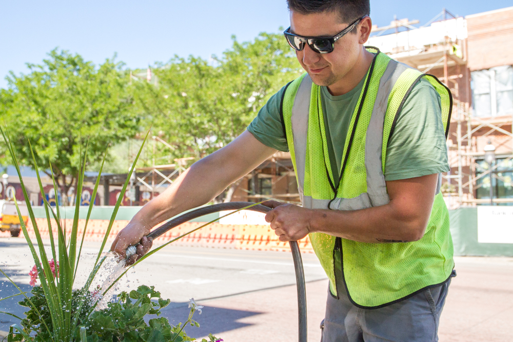 City of Glenwood Springs worker Arturo Cordova watering one of the 64 pots along Grand avenue and Seventh Street. The flower pots will continue getting watered two to three times a week throughout the summer.