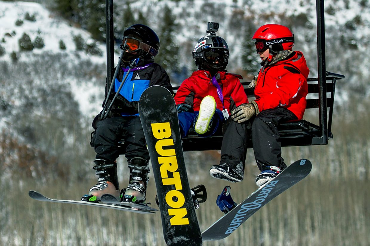 A group of young snowboarders and a skier peacefully take the chair lift together to the top of Sunlight resort.