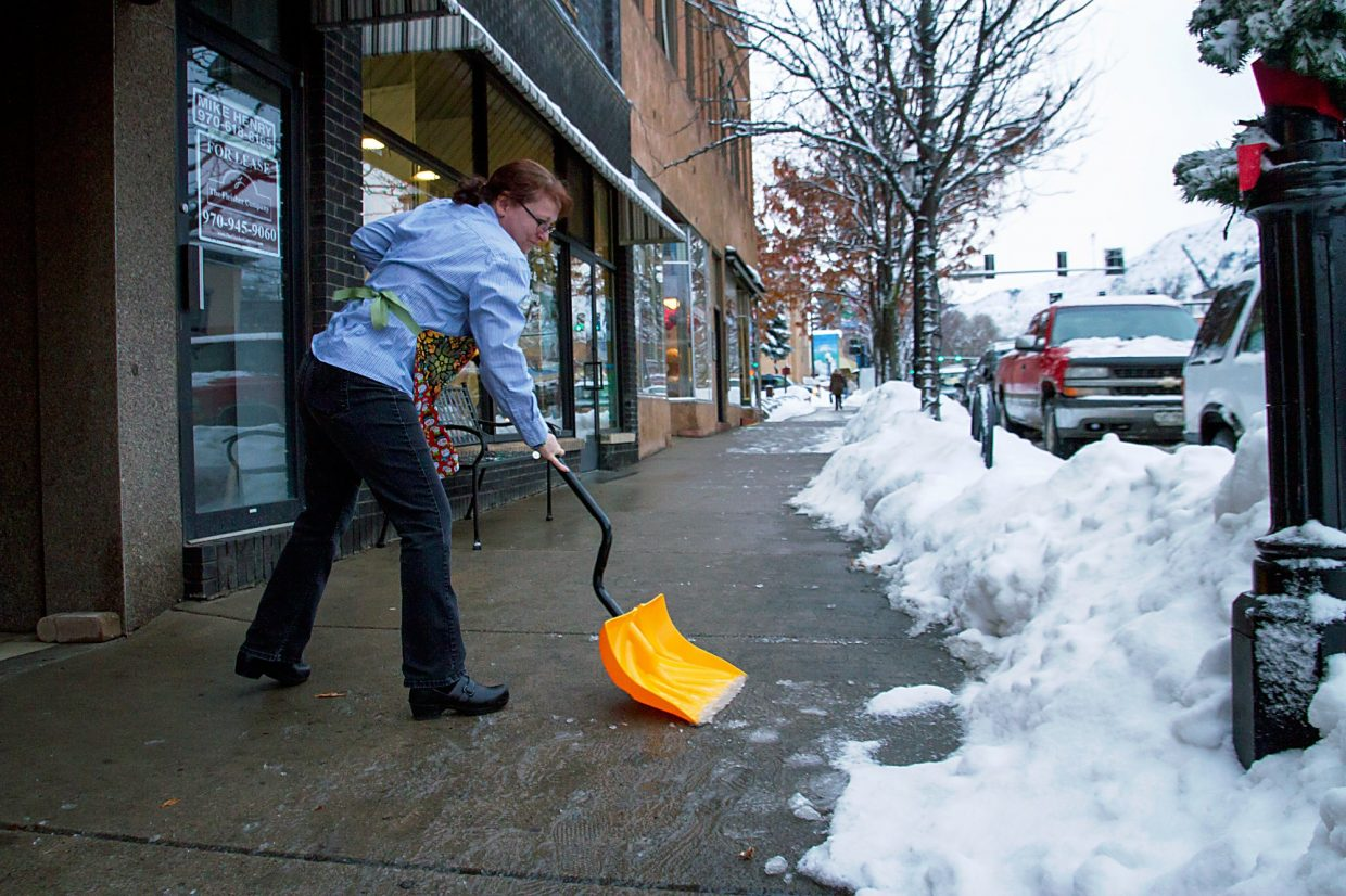Elizabeth Axthelm, the owner of Glenwood Sew shovels the sidewalk infront of her business on Grand Ave.  The endless supply of snow over the last few days have kept many business and home owners busy shoveling multiple times a day.