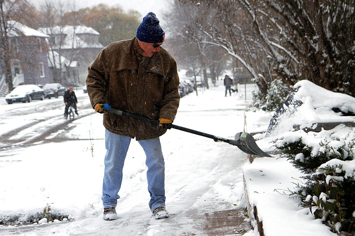Christopher Mullen Post Independent Jim Douglas shovels snow from the sidewalk in front of his Glenwood Springs home, November 13.