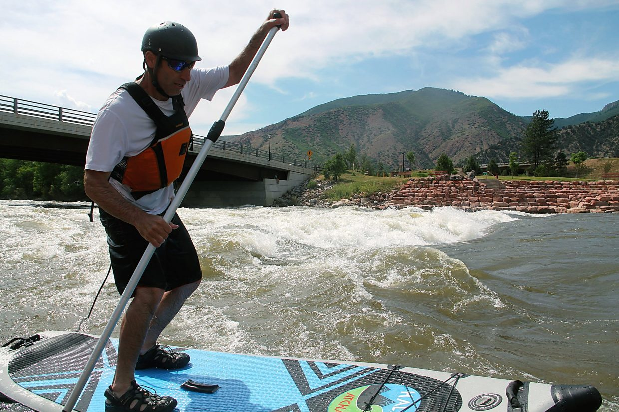 Wade Mooradin rides his stand-up paddleboard at the Wave in Glenwood Springs.