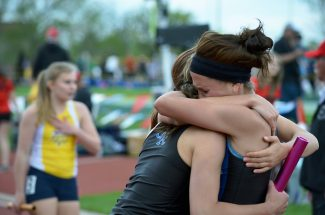 Coal Ridge High School senior Amanda Wenzel hugs team members Paige Ryan and Mariela Martinez (not shown) after the Titans won the state championship in the 4x200-meter relay during the Class 3A State Championships on Friday in Lakewood.