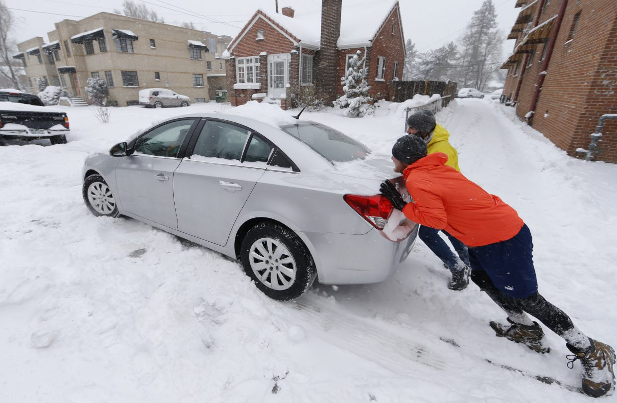 John Malsbary, front right, joins forces with Joe Gray, back right, to push a sedan driven by Rebecca Conway out of a curbside spot where the vehicle was stuck early Tuesday in Denver.