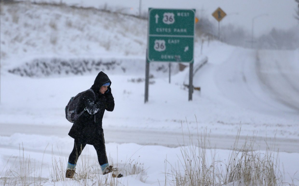 A pedestrian crosses a road Tuesday after a night of heavy snowfall in Boulder. The biggest winter storm to hit the Denver area so far this season left most schools closed and created some havoc on the roads for those forced to commute.