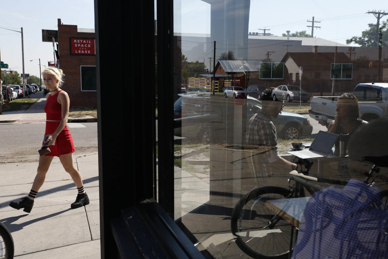 ADVANCE FOR USE TUESDAY, JULY 5, 2016 AND THEREAFTER-In this June 29, 2016 photo, patrons sit in a coffee shop in the trendy RINO neighborhood of Denver. The city is one of the fastest-growing in the nation, with a 3.3 percent unemployment rate and a housing market that has risen 45 percent since 2012. Once dependent on the energy industry for jobs, the city has diversified its economy enough that the recent downturn in fuel prices has barely hampered a booming economy powered by technology and health care jobs. (AP Photo/Brennan Linsley)