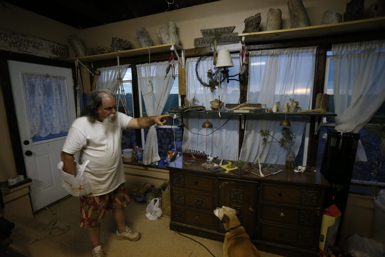 ADVANCE FOR USE TUESDAY, JULY 5, 2016 AND THEREAFTER- In this June 30, 2016 photo, Navy veteran and out of work chef Bill Hendren talks with his dog in a cottage on the property of a landowner who is allowing him to stay rent-free for a year in exchange for work, outside Manzanola, Colo., in Otero County. Hendren, 55, once worked in Texas nightclubs but there's nothing comparable in Otero County, where the largest town has a population of 6,900.