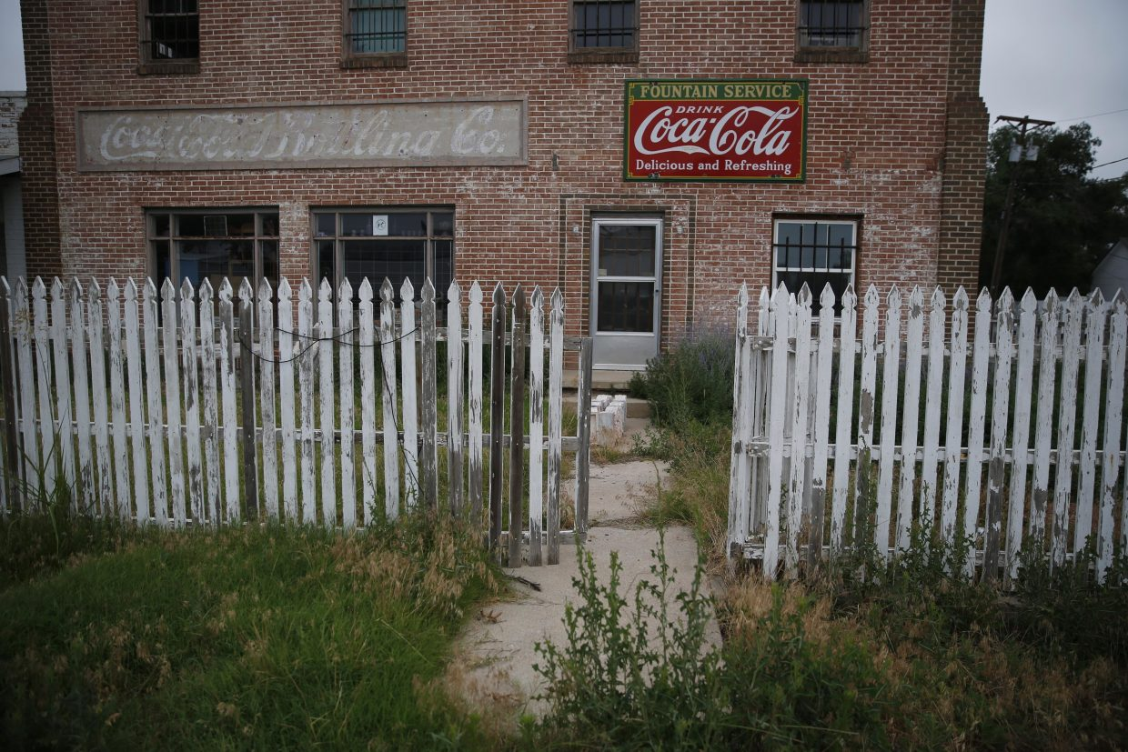 ADVANCE FOR USE TUESDAY, JULY 5, 2016 AND THEREAFTER-In this July 1, 2016 photo, weeds grow around an old building and picket fence in Rocky Ford, Colo., in Otero County, a rural and increasingly impoverished part of southern Colorado. Two different economic worlds are writ large in this state. It is among those with the greatest economic gap between urban and rural areas, according to an Associated Press review of Economic Innovation Group data. (AP Photo/Brennan Linsley)