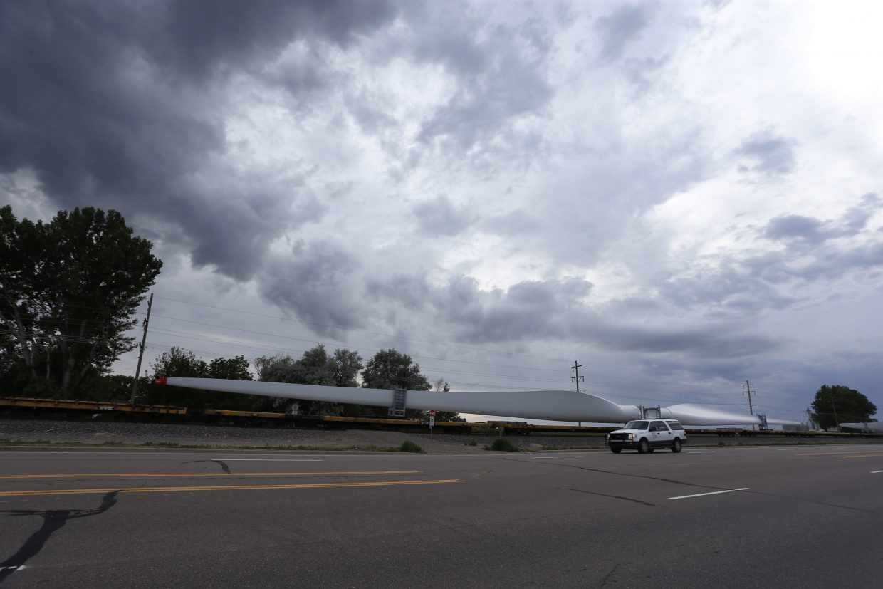ADVANCE FOR USE TUESDAY, JULY 5, 2016 AND THEREAFTER-In this June 30, 2016 photo, a train carries blades for wind turbines bound for another state through Rocky Ford, Colo., in Otero County. Rural areas have been especially slow to recover from the Great Recession that began in 2008: The most recent study by the U.S. Department of Agriculture found that, as of 2014, rural areas still had not regained all the jobs lost in the recession while metropolitan areas had. (AP Photo/Brennan Linsley)