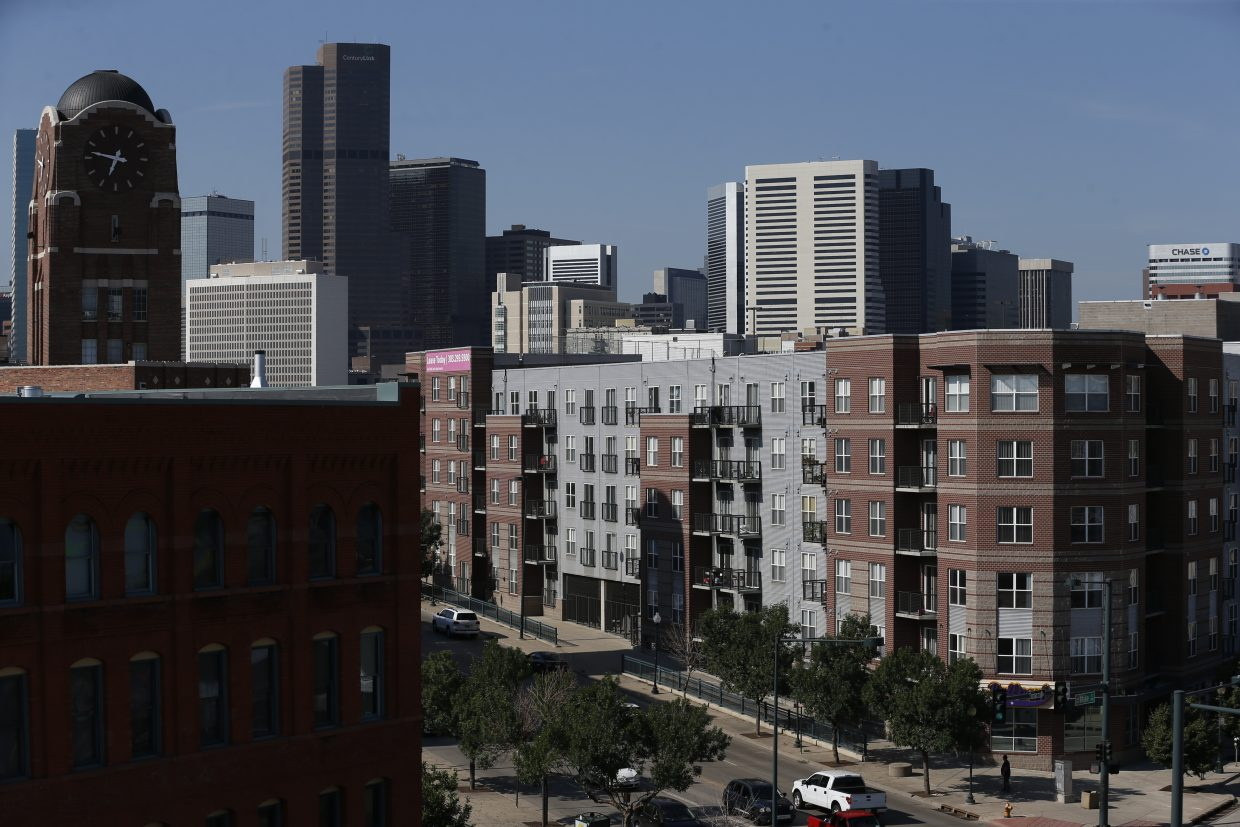 ADVANCE FOR USE TUESDAY, JULY 5, 2016 AND THEREAFTER-In this June 29, 2016 photo, new apartment buildings line a street in trendy downtown Denver. One of the fastest growing economies in the nation, the city's current success contrasts with the economic slump that often defines life in rural Colorado. (AP Photo/Brennan Linsley)