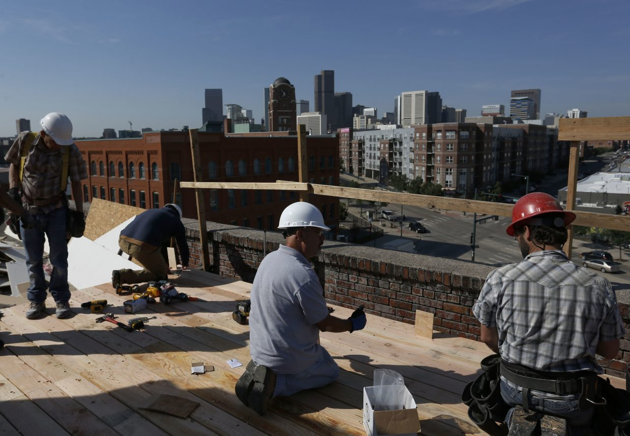 ADVANCE FOR USE TUESDAY, JULY 5, 2016 AND THEREAFTER-In this June 29, 2016 photo, a construction team works on the rooftop of a high-end office structure in downtown Denver. One of the fastest growing economies in the nation, Denver's current success has brought with it a high demand for new housing and office space. (AP Photo/Brennan Linsley)