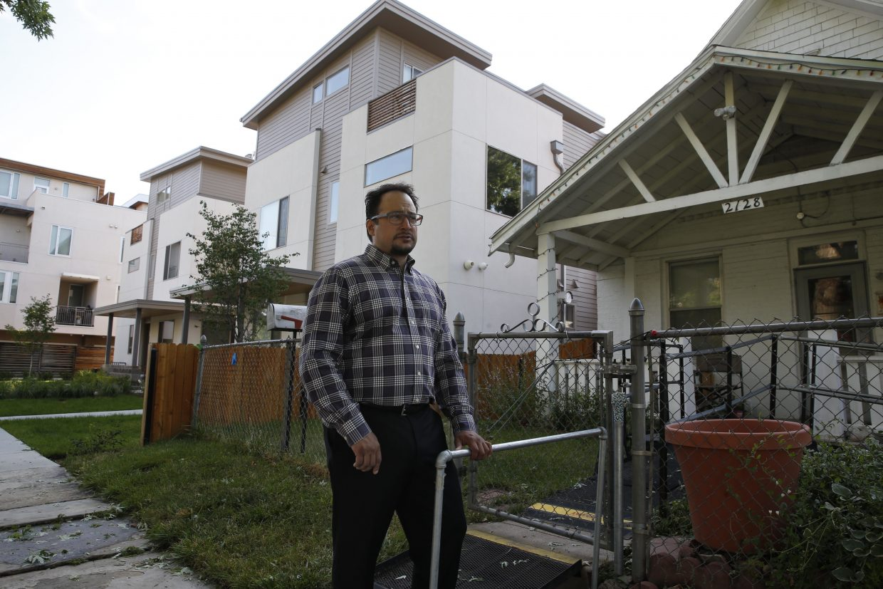 ADVANCE FOR USE TUESDAY, JULY 5, 2016 AND THEREAFTER-In this June 29, 2016 photo, Denver City Councilman Rafael Espinoza stands outside his home in Denver, next to new homes on the left. Espinoza is an architect who was elected to Denver's city council last year as part of a group of candidates questioning the value of Denver's runaway growth. He has seen his neighborhood of modest bungalows occupied by largely Latino families abruptly transformed into a collection of condominiums housing affluent professionals. He worries that the character of the city has changed. (AP Photo/Brennan Linsley)