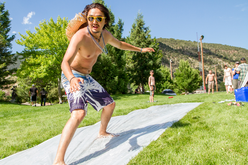Altai Chuluun took advantage of a water slip-n-slide to cool off on the hot afternoon before the fireworks.