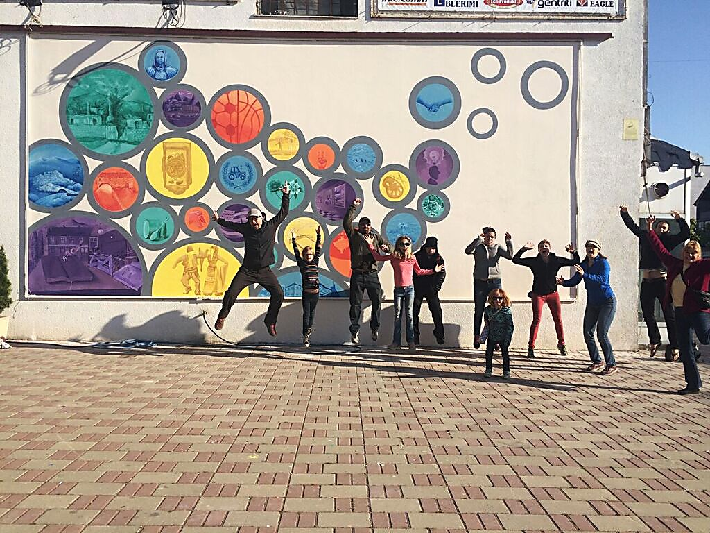 Artists from Colorado and Albanian artists from Kosovo celebrate after completing a mural in Viti, Kosovo, in 2015.