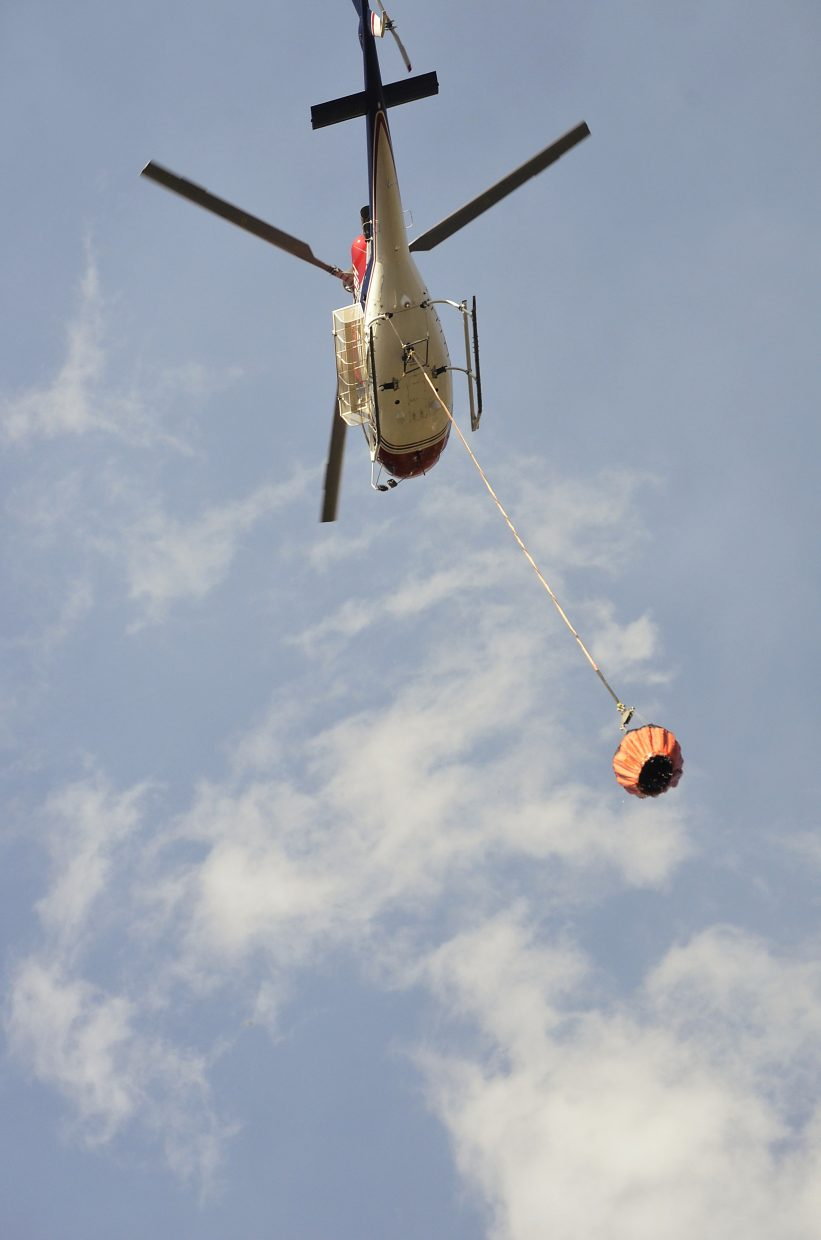 A helicopter joins the fight against Friday's wildfire.
