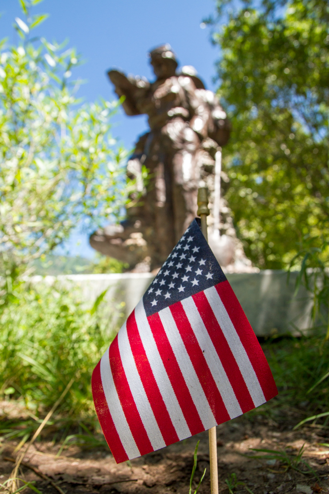 A flag from Monday's Independence Day events flutters Wednesday in front of the Storm King firefighters memorial at Two RIvers Park in Glenwood Springs. The 14 firefighters died 22 years ago Wednesday protecting Glenwood from the growing fire on the mountain west of town.