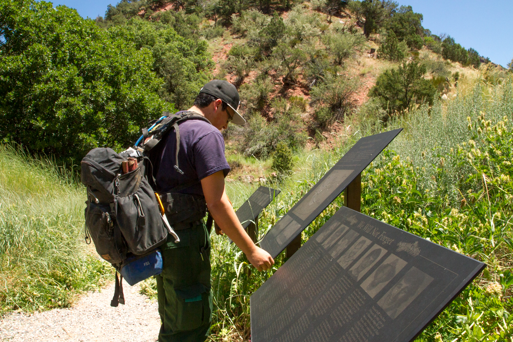 Firefighter Marteen Herrera with the Upper Colorado River Interagency Fire Managment Unit looks at the plaque at the Storm King Mountain Memorial trailhead.