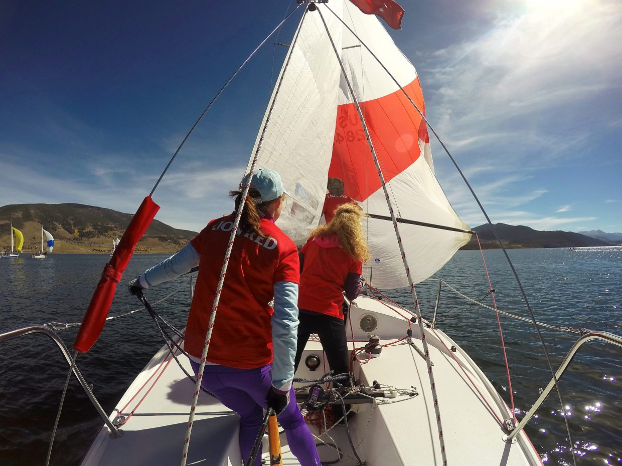 A J22 crew walks the deck to rig sails on Lake Dillon.