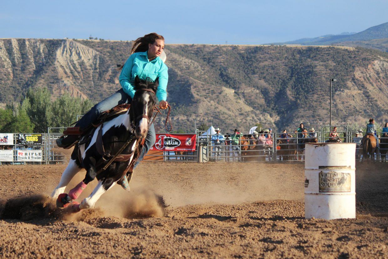 Kaitlyn Harris competes in the family barrel racing event during family rodeo night at the 2016 Garfield County Fair and Rodeo in Rifle on Monday.